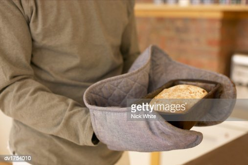 Unrecognizable Person Wearing Oven Gloves and Holding a Baking Tray with a Freshly Baked Loaf Inside : Stock Photo