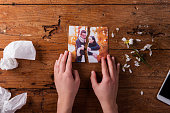 Unrecognizable woman holding torn picture of couple in love. Ended relationship. Crying.Valentines day composition. Studio shot on brown wooden background.