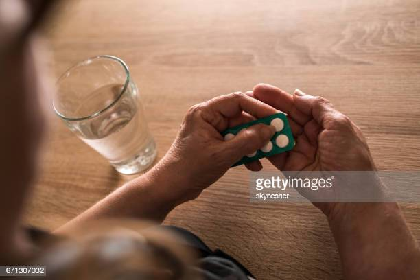 Unrecognizable senior woman taking a pill with a glass of water.
