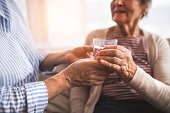 Two unrecognizable senior women at home, holding a glass of water. Family and generations concept.