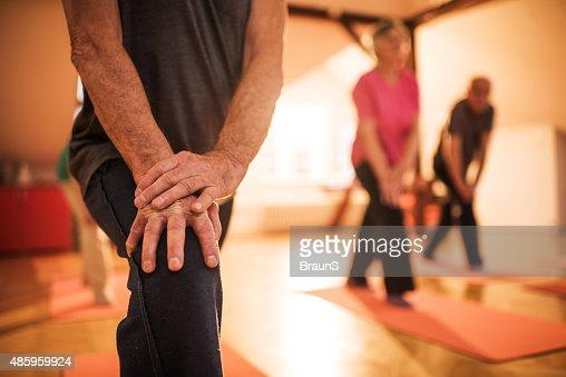 Irreconocible jubilados haciendo ejercicios de estiramiento en la formación.