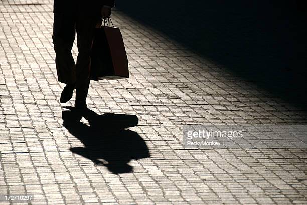 Recortados sombra homem caminha ao ar livre com Saco de Compras