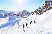 skiers on beautiful ski slope in Alps, people on  winter holidays