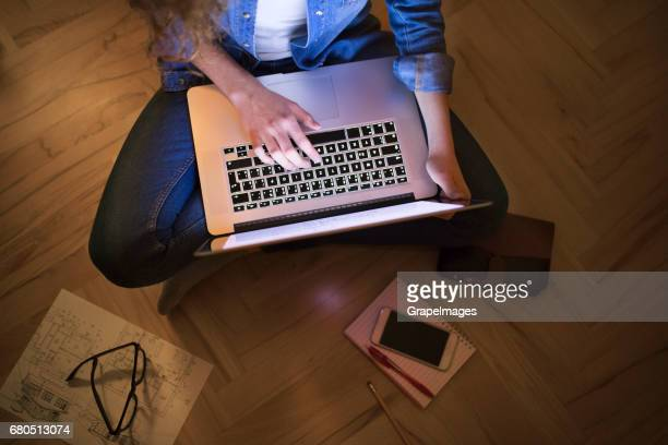 Unrecognizable teenage girl with tablet sitting on the floor, studying at night