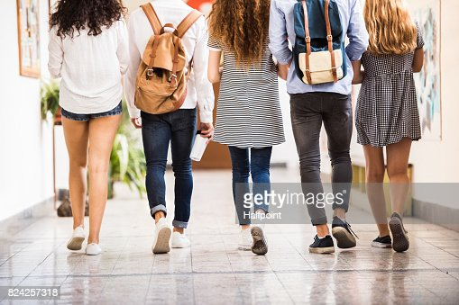 Unrecognizable teenage students in high school hall. : Stock Photo