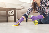 Unrecognizable woman polishing wooden floor. Young girl in protective gloves washing apartment, spring cleaning concept, copy space, closeup