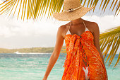 unrecognizable woman in big straw hat, white bikini and orange sarong poses on a tropical Caribbean beach