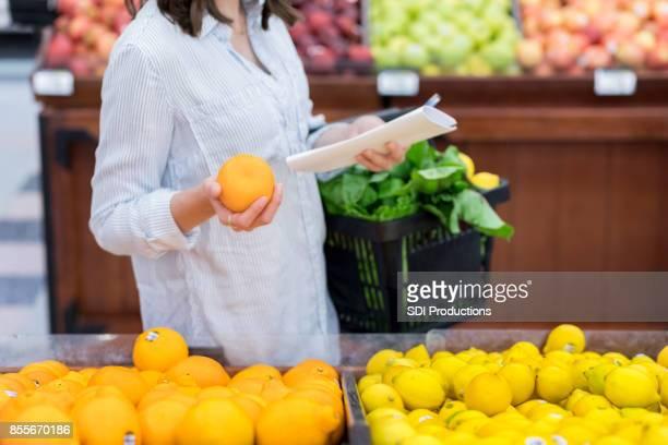 Unrecognizable woman shops for oranges