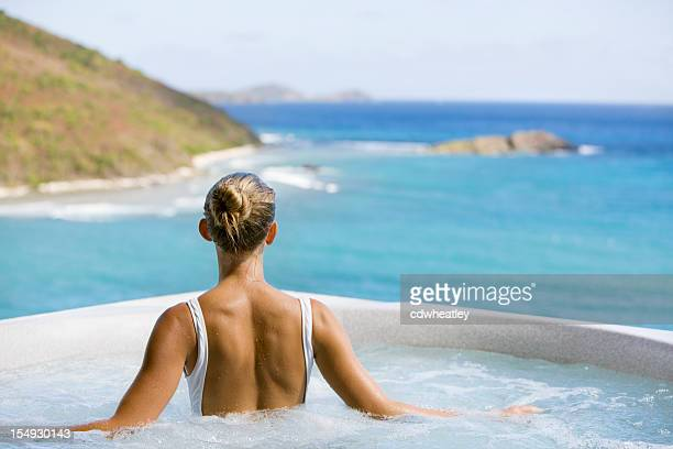 unrecognizable woman soaking in a jacuzzi whirlpool
