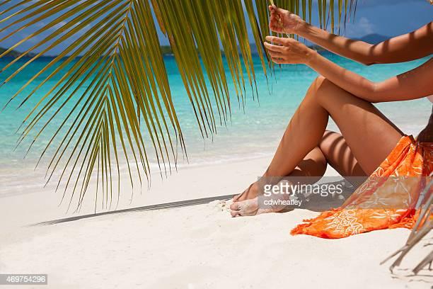 Donna irriconoscibile prendere il sole su una spiaggia tropicale a Caraibi
