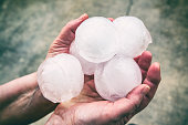 An unrecognizable women is showing a small group of very big ice hailstones just fallen from the sky with violence, holding in her hands. This picture was taken in selective focus on ice, white color