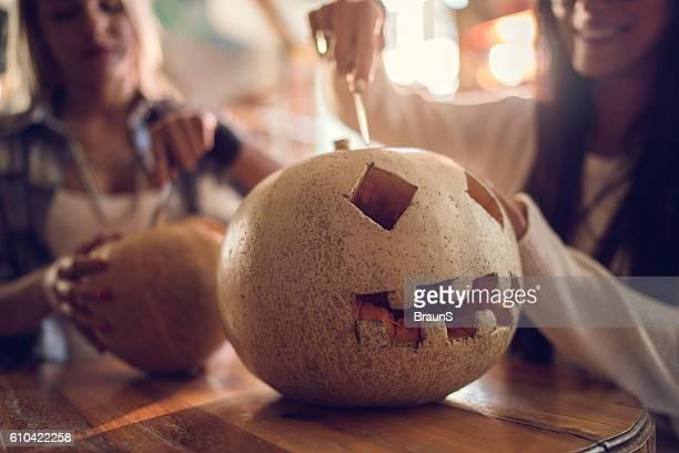 Unrecognizable women making Jack O' Lantern for Halloween.