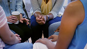 An unrecognizable group of women sit in a group therapy circle together.  One woman has her hands clasped.