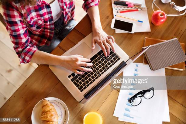 Unrecognizable young woman at home, working on laptop, studying