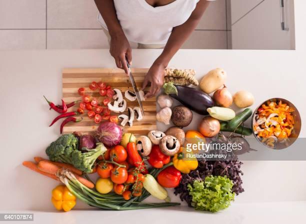 Unrecognized women preparing fresh healthy salad.