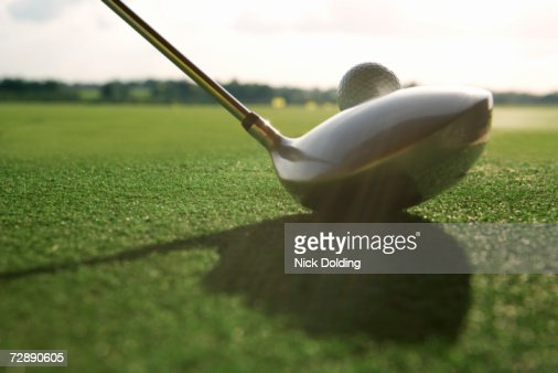 Unseen golfer teeing off, close up on driver, close-up