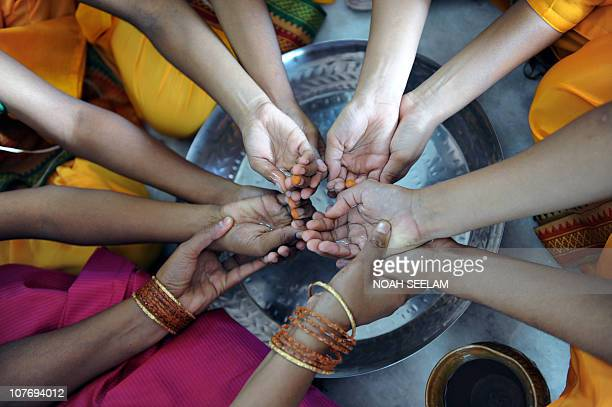 Unseen Indian Hindu woman priest Acharya Savitha performs a religious ritual as she teaches young girls aspiring to become priests at the Pani...