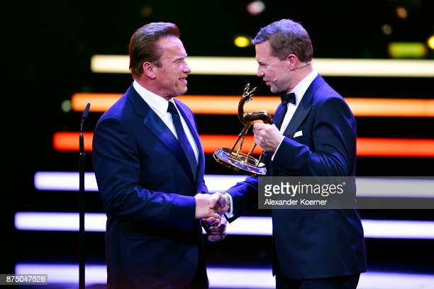 'Unsere Erde' Award Winner Arnold Schwarzenegger and Steffen Seibert are seen on stage during the Bambi Awards 2017 show at Stage Theater on November...