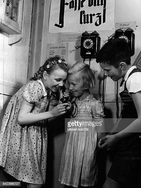 Unterricht in einer Volksschule in der der Lehrer ein sog Verkehrszimmer eingerichtet hat Kinder üben dasTelefonieren Über dem Telefon der Hinweis...