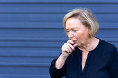 Unwell elderly lady having a coughing fit holding her hand to her mouth conceptual of seasonal flu, allergies or choking over blue with copy space