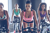 Young beautiful women with perfect bodies in sportswear looking at camera while cycling at gym