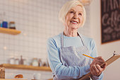 At your service. Pleasant cheerful elderly woman in an apron working as a waitress in a coffee shop and taking notes about her clients order while smiling