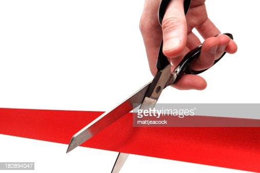Up-close shot of scissors cutting through a red ribbon