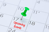 Upcoming Events written on a calendar with a green push pin to remind you and important appointment.