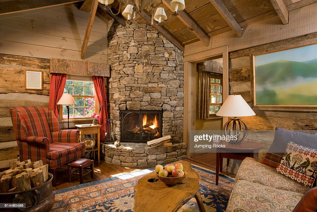 Upholstered chair next to rustic stone fireplace with lit fire.