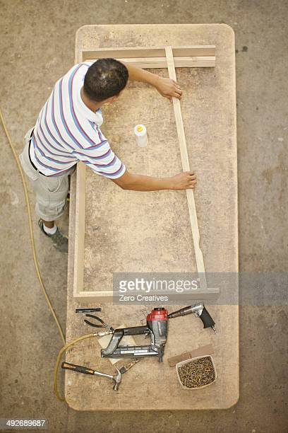 Upholsterer constructing a wooden frame on table