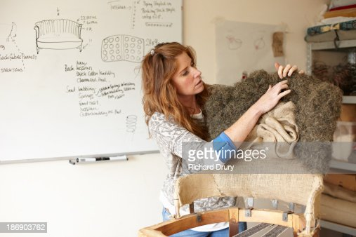 Upholsterer fitting horse hair to old chair : Stock Photo