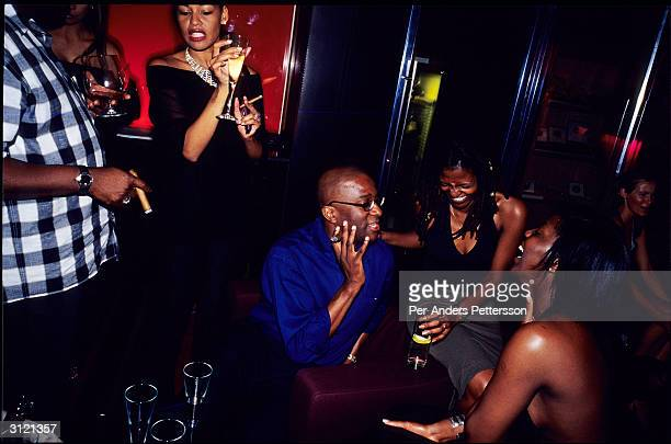 Upper class black people drink champagne and smoke cigars in the champagne bar at Kilimanjaro an upper class club May 5 2003 in Melrose Arch a suburb...