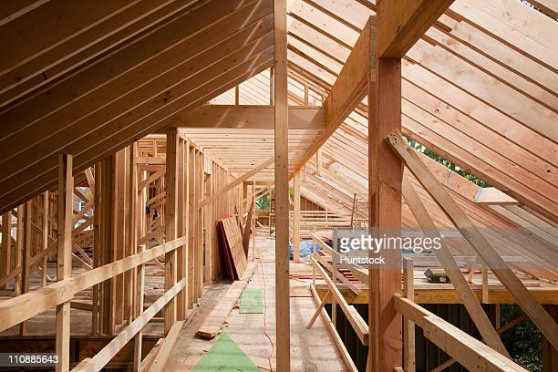 Upper floor room framing and rafters of a house under construction