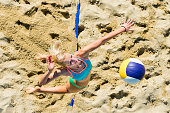 Upper view of young female beach volley player serving the ball