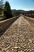 View of ancient Roman bridge in Molinaseca, Spain. The historic bridge made of pebbles is part of St James Way, a pilgrimage route walked by  many thousands every year.