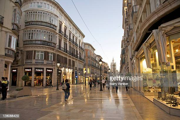 Upscale shops and shoppers at dusk on pedestrian street Calle de Larios, Malaga, Costa del Sol, Andalucia, Spain
