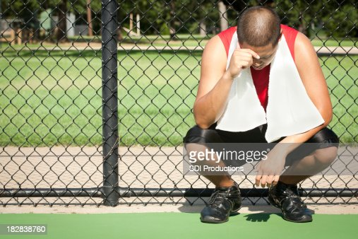 Upset Athlete Kneeling Next to Fence