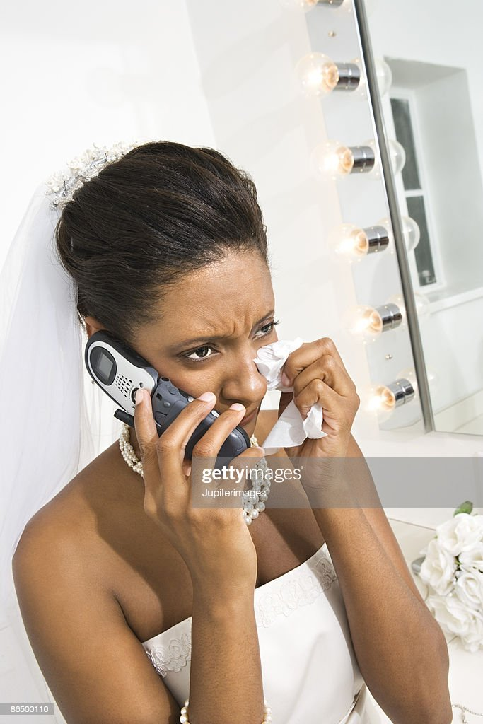 Upset bride using cell phone : Stock Photo