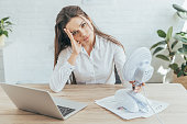 upset businesswoman sitting at workplace with paperwork, laptop and electric fan