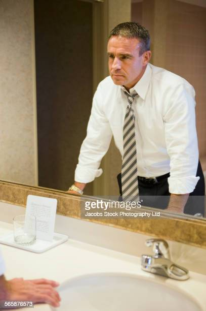 Upset Caucasian businessman staring in hotel bathroom mirror