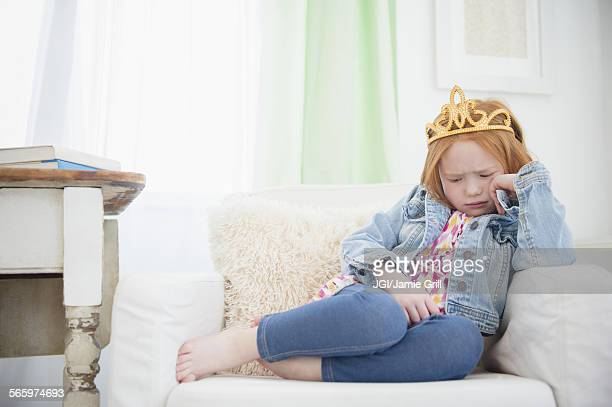 Upset Caucasian girl pouting in armchair