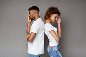 Break up, relationship problems. Unhappy african-american man and woman standing back to back on gray background, copy space