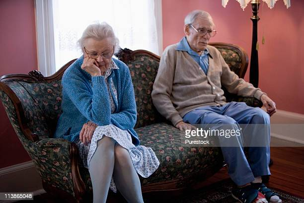 Upset elderly couple sitting on sofa