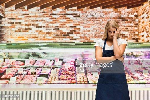 Upset female butcher in shop : Foto de stock