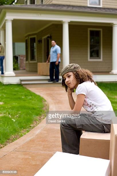Upset girl sitting on moving boxes outside house