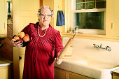 A grumpy granny in curlers and cat glasses stands with a bowl of plastic fruit and rolling pin in her kitchen near the sink. More granny images.