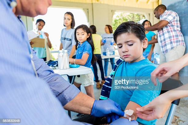 Upset hispanic boy getting a flu shot at free clinic