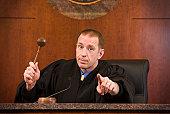 Upset judge swinging gavel and pointing