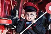 Portrait of a cute little child boy with annoyed facial expression as nostalgic railroad conductor and metal-rimmed glasses, cap and signaling disk