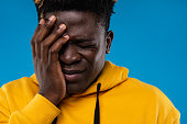 Feeling frustrated. Close up portrait of frustrated male in yellow hoodie touching face as if forgot something important. Isolated on blue background